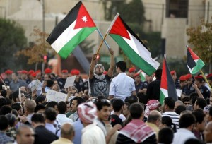 Jordanians wave their national flag and shout slogans during a protest near the Israeli embassy in Amman on September 15, 2011 to demand that the government expel the Jewish state's envoy and scrap the joint 1994 peace treaty. AFP PHOTO/KHALIL MAZRAAWI (Photo credit should read KHALIL MAZRAAWI/AFP/Getty Images)
