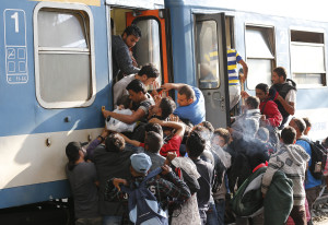 Migrants struggle to board a train at the railway station in Budapest, Hungary, Thursday, Sept. 3, 2015. Over 150,000 migrants have reached Hungary this year, most coming through the southern border with Serbia, and many apply for asylum but quickly try to leave for richer EU countries.(AP Photo/Frank Augstein)