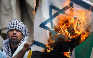 Pro Palestinian protester burns an Israeli flag during demonstration banned by police, in support of Gaza in central Paris, July 26, 2014. REUTERS/Benoit Tessier (FRANCE - Tags: POLITICS CIVIL UNREST)